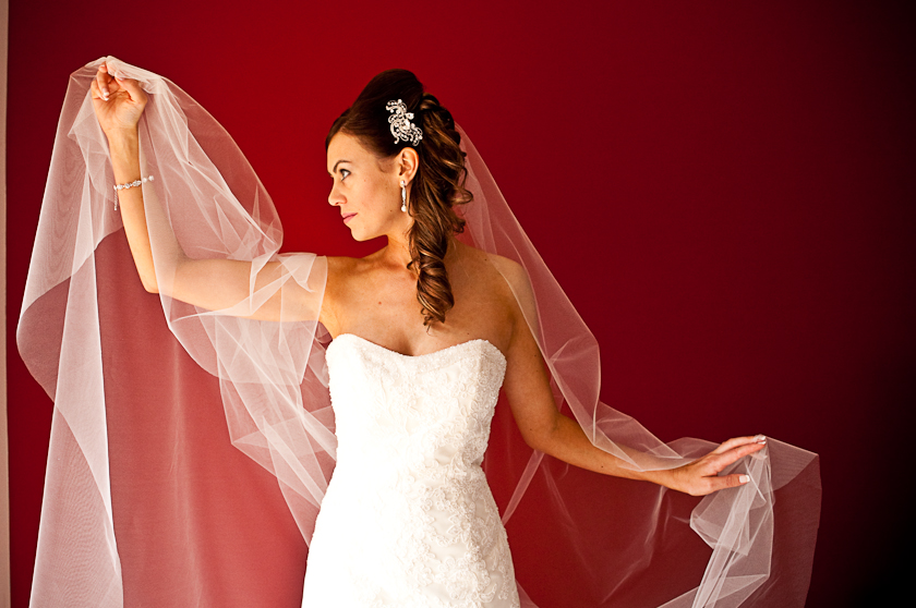 bride with veil and red coloured wall