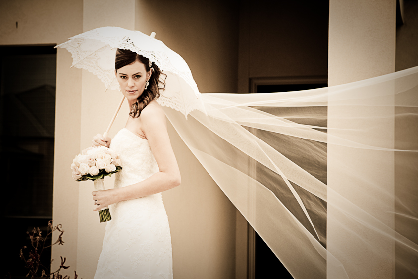 Bride with brolly and veil blowing in the wind